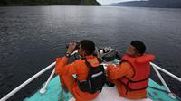 Tim SAR menggunakan teropong saat proses pencarian korban KM Sinar Bangun di Danau Toba, Sumatra Utara, Rabu (20/6). Sebelumnya, KM Sinar Bangun yang mengangkut 128 penumpang tenggelam di Danau Toba pada Senin (18/6) sore. (AP/Binsar Bakkara)