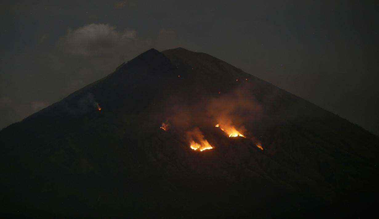 Api membakar hutan lereng Gunung Agung setelah terjadinya lontaran batu pijar dari kawah terlihat dari Karangasem, Bali, Selasa (3/7). PVMBG mencatat terjadinya erupsi Gunung Agung secara strombolian dan terdengar pula suara dentuman (AP/Firdia Lisnawati)