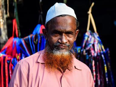 Dalam gambar yang diambil pada 24 Desember 2018, penjual sayur bernama Siddikur Rahman berpose dengan janggut oranye di Dhaka. Belakangan ini, pria-pria Muslim Bangladesh keranjingan berpenampilan dengan janggut warna-warna terang seperti merah hingga oranye. (MUNIR UZ ZAMAN / AFP)