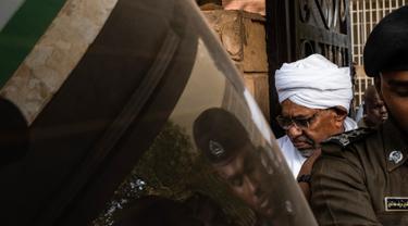 Mantan Presiden Sudan, Omar al-Bashir, dikawal setelah menghadap jaksa untuk pembacaan dakwaan terkait kasus korupsi di ibu kota Khartoum, Minggu (16/6/2019). Ini merupakan penampilan pertamanya di hadapan publik sejak kudeta penggulingan dirinya pada April lalu. (Yasuyoshi CHIBA/AFP)