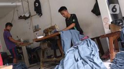 Para pekerja menyelesaikan pembuatan seragam sekolah di usaha konveksi skala rumah tangga Kebayoran Lama, Jakarta, Kamis (9/7/2020). Pandemi virus corona COVID-19 berdampak pada sepinya pesanan pembuatan seragam sekolah. (Liputan6.com/Angga Yuniar)