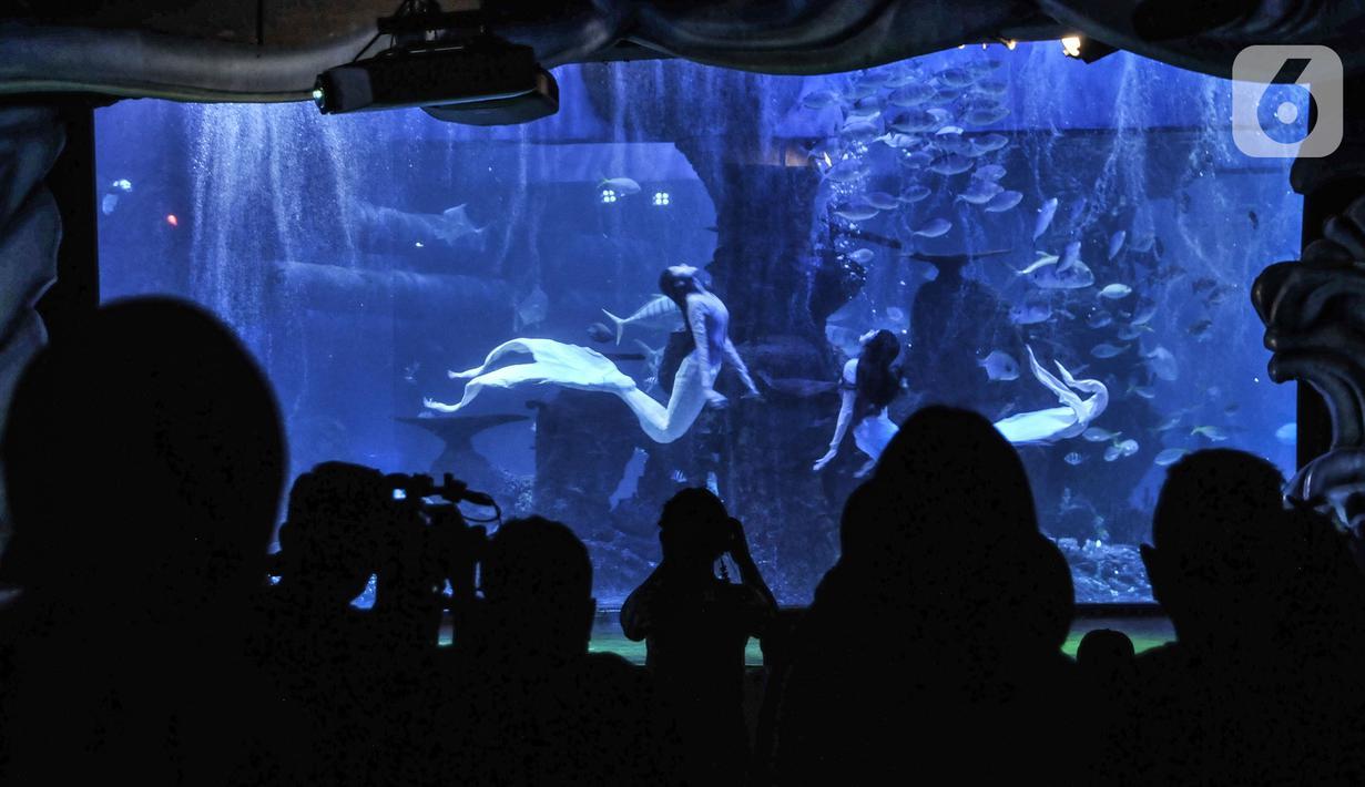 Pengunjung menyaksikan pertunjukan bawah air yang menampilkan putri duyung di Jakarta Aquarium & Safari (JAQS), Neo Soho Mall, Jakarta, Rabu (21/4/2021). JAQS menjadi salah satu lokasi alternatif warga dalam mengisi waktu jelang berbuka puasa atau ngabuburit. (merdeka.com/Iqbal S. Nugroho)