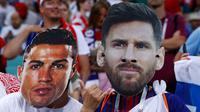 Suporter mengenakan topeng bintang Portugal, Cristiano Ronaldo dan bintang Argentina, Lionel Messi sebelum laga babak perempat final Piala Dunia 2018 antara Rusia dan Kroasia di Stadion Olimpiade Fisht, Sochi, Sabtu (7/7). (AP Photo/Manu Fernandez)
