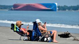 Rachel (kiri) dan Sarah Mitchell bermain ponsel saat berjemur dengan pemandangan kapal kargo Golden Ray yang terbalik di lepas pantai negara bagian Georgia, Amerika Serikat, Minggu (8/9/2019). Kapal tersebut dilaporkan memiliki 23 awak dan seorang nakhoda . (AP Photo/Terry Dickson)