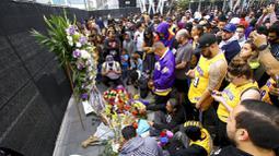 Fans LA Lakers tampak sedih saat berkumpul di Staples Center, Minggu (26/1/2020). Legenda basket NBA, Kobe Bryant, wafat dalam kecelakaan helikopter di Calabasas, California. (AP/Matt Hartman)
