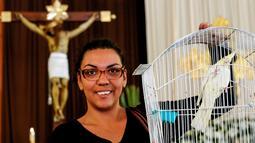 Seorang wanita membawa burung peliharaannya untuk diberkati di Gereja Santo Fransiskus Asisi, yang menandai Hari Hewan Dunia di Guadalajara, Meksiko, Kamis (4/10). Perayaan Santo Fransiskus dipercaya sebagai Santo pelindung binatang. (AFP/Ulises Ruiz)