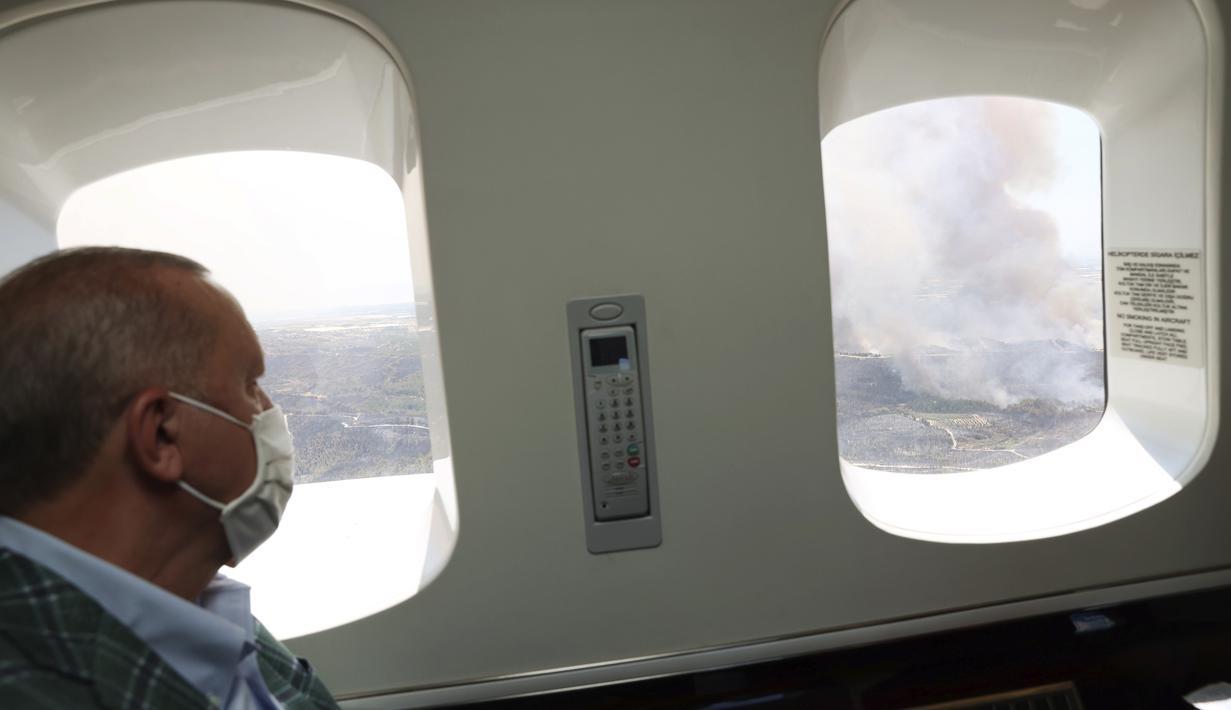 Presiden Turki Recep Tayyip Erdogan menyaksikan dari pesawat kebakaran hutan di Manavgat, Antalya, Turki, Sabtu (31/7/2021). Korban tewas akibat kebakaran hutan di kota-kota Mediterania Turki naik menjadi enam orang setelah dua pekerja hutan tewas. (Turkish Presidency via AP, Pool)