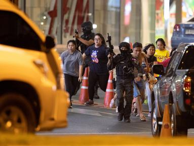 Tentara mengawal pengunjung yang keluar dari mal Terminal 21 Korat saat terjadi penembakan di Nakhon Ratchasima, Thailand, Minggu (9/2/2020). Seorang tentara tanpa alasan jelas memberondong tembakan di mal Terminal 21 Korat. (AP Photo/Sakchai Lalitkanjanakul)