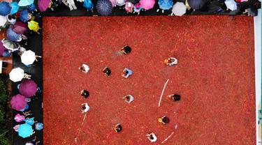Suasana kompetisi makan cabai di Ningxiang di provinsi Hunan tengah, China (8/7). Pemenang dalam kontes ini telah memakan 5 cabai dalam waktu satu menit. (AFP Photo)