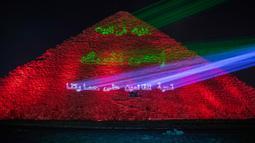 Kementerian barang antik Mesir menerangi Piramida Besar Mesir dengan pesan dukungan bagi tenaga kesehatan yang memerangi pandemi corona Covid-19 di Giza, Senin (30/3/2020). Piramida tersebut menampilkan pesan dalam bahasa Arab dan Inggris dalam cahaya berwana biru dan hijau. (AP/Nariman El-Mofty)