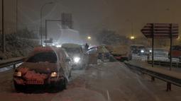 Sejumlah mobil terjebak salju tebal yang menyelimuti Jalan Lingkar M30 di Madrid, Spanyol, Jumat (8/1/2021). Salju tebal memotong dua jalan lingkar di Madrid, M30 dan M40. (OSCAR DEL POZO/AFP)