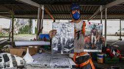"""Seniman Thiago Mundano memegang salinan """"The Coffee Farmer"""" karya mendiang pelukis Brasil Candido Portinari dan versi skala kecil dari muralnya """"The Forest Brigadier"""" di Sao Paulo, Jumat (15/10/2021). Mundano mencampur abu kebakaran hutan di seluruh Brasil ke dalam catnya. (AP/Marcelo Chello)"""