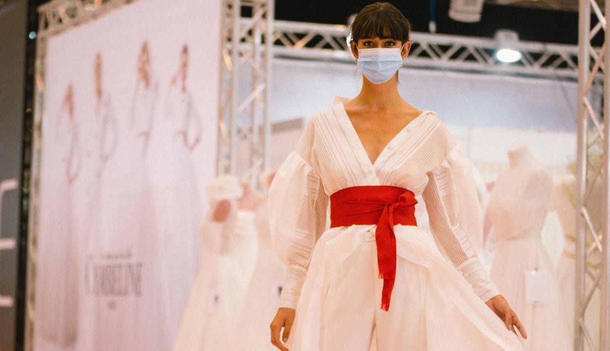 Seorang model yang mengenakan masker memperagakan gaun pengantin di pameran dagang European Bridal Week di Essen, Jerman, pada 5 Juli 2020. European Bridal Week, sebuah pameran dagang internasional tentang pernikahan, diselenggarakan mulai 4 hingga 6 Juli. (Xinhua/Tang Ying)
