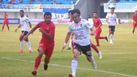 Bek Bali United, Michael Orah (putih) berduel dengan pemain Timnas U-22, Asnawi Mangkualam di Stadion Mandala Krida, Yogyakarta, Minggu (8/9/2019). (Bola.com/Vincentius Atmaja)