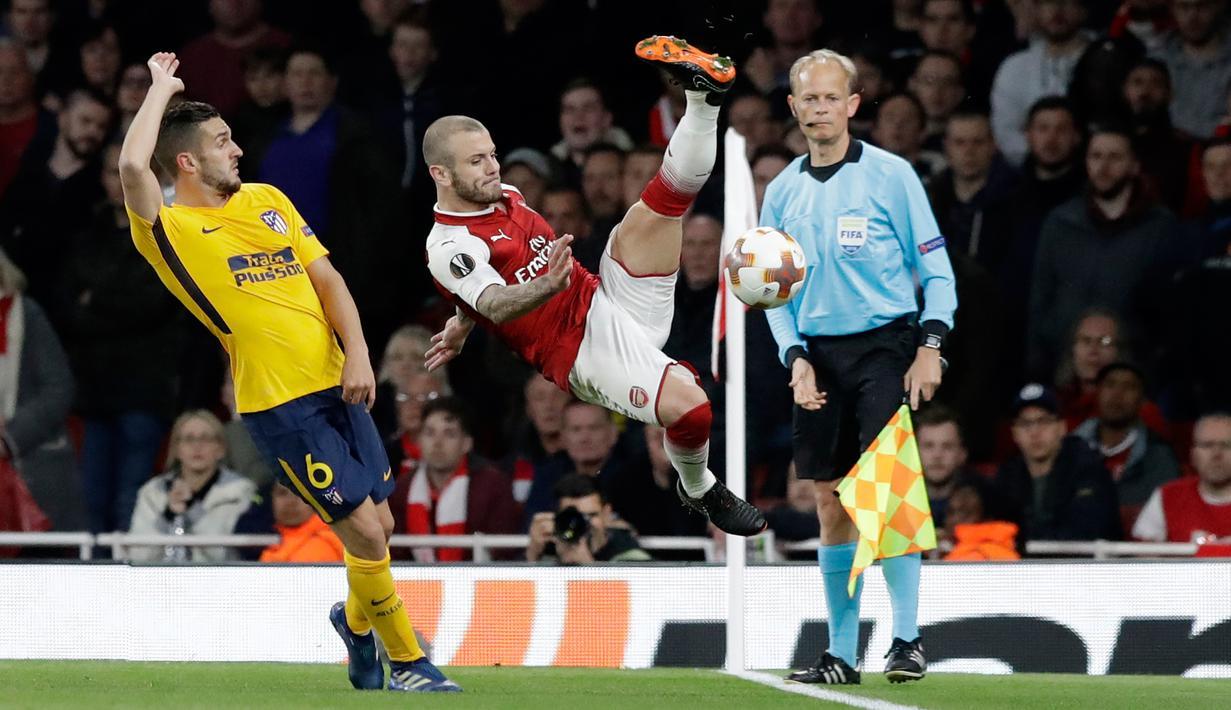 Pemain Arsenal, Jack Wilshere mencoba menyelamatkan bola  dari pemain Atletico Madrid, Koke pada laga leg pertama semifinal Liga Europa di Stadion Emirates, Kamis (26/4). Arsenal hanya meraih hasil seri 1-1 saat menjamu Atletico Madrid.  (AP/Matt Dunham)