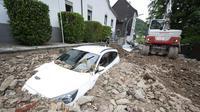 Sebuah mobil tertimbun puing-puing setelah hujan lebat menyebabkan banjir dan kerusakan besar di distrik Hohenlimburg di Hagen, Jerman, Kamis (15/7/2021). (Julian Stratenschulte/dpa via AP)