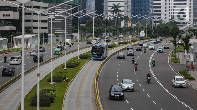 Arus lalu lintas kendaraan di Jalan Sudirman, Jakarta, Senin (13/4/2020). Hari ke-4 penerapan Pembatasan Sosial Berskala Besar (PSBB) di DKI yang dimulai sejak 10 April hingga 23 April 2020, arus lalu lintas di ruas jalan protokol  tersebut masih ramai kendaraan. (Liputan6.com/Faizal Fanani)