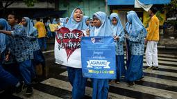 Sejumlah pelajar membawa spanduk saat menggelar demonstrasi menolak perayaan Hari Valentine di Surabaya, Jawa Timur, Kamis (14/2). Penolakan terjadi karena Valentine dinilai mempromosikan pergaulan bebas. (Juni Kriswanto/AFP)