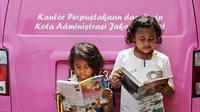 Anak-anak membaca buku yang disediakan perpustakaan keliling di kawasan Tanah Abang, Jakarta, Minggu (11/10). Keberadaan perpustakaan keliling untuk meningkatkan minat baca pada anak-anak. (Liputan6.com/Immanuel Antonius)