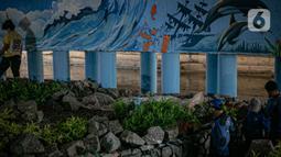 Mural buatan mahasiswa Institut Kesenian Jakarta (IKJ) di kolong Jembatan Pegangsaan, Menteng, Jakarta, Selasa (26/1/2021). Pembuatan mural tersebut merupakan bagian dari pembangunan taman kolong jembatan oleh Pemprov DKI Jakarta. (Liputan6.com/Faizal Fanani)