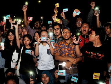 Sejumlah aktivis menyalakan senter saat melakukan aksi solidaritas #MelawanGelap di depan Istana Merdeka, Jakarta, Jumat (5/8). Aksi tersebut merupakan bentuk dukungan kepada Koordinator Kontras Haris Azhar. (Liputan6.com/Gempur M Surya)