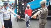 Petugas mengarahkan penumpang yang turun dari bus Antar Kota Antar Provinsi (AKAP) di Terminal bus Kalideres, Jakarta Barat, Senin (17/5/2021). Arus balik pemudik mulai terlihat di sejumlah terminal di Jakarta, salah satunya di Terminal Kalideres. (Liputan6.com/Angga Yuniar)