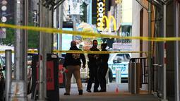 Petugas polisi melakukan pemeriksaan di lokasi penembakan di Times Square di New York, AS (8/5/2021). Penembakan brutal terjadi di kawasan Times Square, dekat West 44th St. dan 7th Ave di New York yang mengakibatkan 3 orang terluka termasuk bocah perempuan berusia 4 tahun. (AFP/Kena Betancur)