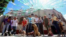Orang-orang membawa hewan peliharaan mereka untuk diberkati di Gereja Santo Fransiskus Asisi, yang menandai Hari Hewan Dunia di Guadalajara, Meksiko, Kamis (4/10). Perayaan Santo Fransiskus dipercaya sebagai Santo pelindung binatang. (AFP/Ulises Ruiz)