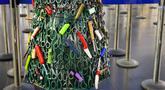 Pohon Natal yang dirakit dari barang-barang sitaan di Bandara Vilnius, Lithuania pada 12 Desember 2019. Pohon Natal unik tersebut dibuat dari barang-barang sitaan yang dilarang dibawa ke kabin pesawat. (Photo by Petras Malukas / AFP)