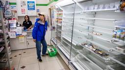 Rak-rak kosong terlihat saat pengunjung membeli  kebutuhan  di sebuah toko, distrik Shinagawa, Tokyo, Sabtu (12/10/2019). Banyak toko-toko perbelanjaan di Jepang yang kehabisan makanan dan minuman akibat warganya yang menimbun makanan untuk menghadapi topan Hagibis. (Odd ANDERSEN / AFP)