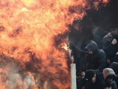 Suporter Ajax Amsterdam mencoba untuk melindungi diri dari ledakan bom molotov selama bentrokan dengan polisi anti huru-hara Yunani sebelum pertandingan Liga Champions melawan AEK Athena di Stadion Olimpiade Athena, Selasa (27/11). (Aris Messinis/AFP)