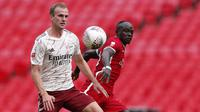 Bek Arsenal, Rob Holding, berebut bola dengan penyerang Liverpool, Sadio Mane, pada laga Community Shield 2020 di Stadion Wembley, Sabtu (29/8/2020) malam WIB. Arsenal menang 5-4 atas Liverpool lewat adu penalti. (Andrew Couldridge/Pool via AP)