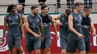 Keceriaan Mesut Ozil dan pemain Arsenal lainnya saat sesi latihan untuk kompetisi pramusim International Champions Cup (ICC) 2018 di Singapura, Rabu (27/5). Menjelang duel kontra Atletico Madrid, Ozil dkk menikmati sesi latihan ringan. (AFP/Roslan RAHMAN)