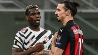 Paul Pogba bersama Zlatan Ibrahimovic usai Manchester United kalahkan AC Milan, 1-0 di leg 2 babak 16 besar Liga Europa 2020/2021, Jumat (19/03/2021) dini hari WIB. (Marco BERTORELLO / AFP)