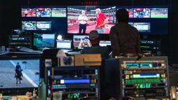 Pemandangan umum menunjukkan orang-orang yang bekerja di ruang kontrol kualitas gambar dari Olympic Broadcasting Services (OBS) di Pusat Siaran Internasional (IBC) di Tokyo pada 28 Juli 2021, selama Olimpiade Tokyo 2020. (AFP/Philip Fong)