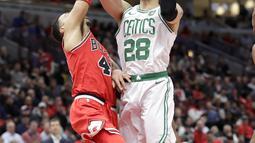 Pebasket Chicago Bulls, Denzel Valentine, berusaha menghadang pebasket Boston Celtics, Jaylen Brown, pada laga NBA di Stadion United Center, Selasa (6/3/2018). Celtics menang 105-89 atas Bulls. (AP/Charles Rex Arbogast)