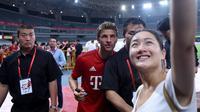 Penyerang Bayern Muenchen, Thomas Mueller berselfie bersama seorang fans usai sesi latihan di Shanghai, China, (19/7/2015). Bayern mengunjungi Cina untuk menggelar Tur Pra-musim. (AFP PHOTO/JOHANNES EISELE)