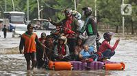 Pengendara sepeda motor menggunakan jasa rakit saat banjir melanda Jalan Ahmad Yani, Cempaka Putih, Jakarta, Minggu (23/2/2020). Banjir yang terjadi dari dini hari tadi melumpuhkan akses jalan tersebut. (Liputan6.com/Herman Zakharia)