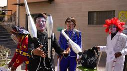 Para badut menghibur orang-orang yang menunggu untuk mendapatkan suntikan vaksin COVID-19 Sinopharm selama kampanye vaksinasi yang menargetkan usia antara 18 dan 30 tahun di Universitas Negeri San Andres di La Paz, Bolivia, Senin (5/7/2021). (AP Photo/Juan Karita)