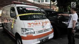 Seorang pria menunjuk ambulans Partai Gerindra yang terparkir di halaman Mapolda Metro Jaya, Jakarta, Kamis (23/5/2019). Ambulans milik Partai Gerindra Tasikmalaya berpelat nomor B 9686 PCF tersebut diamankan polisi karena diduga mengangkut batu dalam Aksi 22 Mei. (merdeka.com/Iqbal Nugroho)