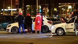Warga Turki berkumpul membawa bendera negara Turki saat menggelar protes di Rotterdam, Belanda (11/3). Belanda melarang Menteri Luar Negeri Turki, Mevlut Cavusoglu untuk mendarat di Rotterdam, Belanda. (AFP/Emmanuel Dunand)