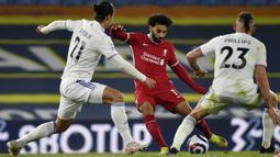 Pemain Liverpool Mohamed Salah (tengah) menggiring bola mencoba melewati pemain Leeds United Pascal Struijk (kiri) dan Kalvin Phillips pertandingan Liga Inggris di Stadion Elland Road, Leeds, Inggris, Senin (19/4/2021). Pertandingan berakhir dengan skor 1-1. (Paul Ellis/Pool via AP)