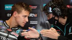 Pembalap Petronas Yamaha, Fabio Quartararo, berbincang dengan teknisinya usai latihan bebas MotoGP Catalunya di Circuit de Barcelona-Catalunya, Jumat (25/9/2020). Pembalab Yamaha, Morbidelli, finish pertama dengan catatan waktu satu menit 39,789 detik. (AFP/Lluis Gene)