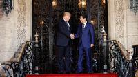 Presiden AS, Donald Trump menyambut kedatangan PM Jepang Shinzo Abe dalam pertemuan mereka di Resor Mar-a-Lago, Florida, Selasa (17/4). Pertemuan digunakan untuk mencari pemahaman bersama mengenai masalah nuklir Korea Utara. (AP/Pablo Martinez Monsivais)