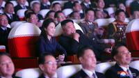 Gambar yang dirilis pada 17 Februari 2021 menunjukkan Pemimpin Korea Utara Kim Jong-un (tengah) dan istrinya Ri Sol Ju menonton pertunjukan di Pyongyang. Ri biasanya sering menemani Kim Jong-un ke acara-acara publik besar, namun dia tidak terlihat sejak Januari 2020. (STR/AFP/KCNA VIA KNS)