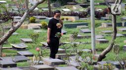 Peziarah mencari makam kerabatnya di Tempat Pemakaman Umum Karet Bivak, Jakarta, Sabtu (18/4/2020). Selama masa PSBB, peziarah yang memasuki kawasan TPU dibatasi dan diwajibkan menggunakan masker sebagai langkah pencegahan penyebaran virus Covid-19. (Liputan6.com/Helmi Fithriansyah)