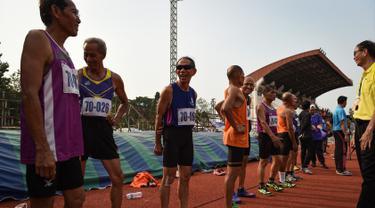 Sejumlah pria lansia bersiap mengikuti lomba sprint 400 meter dalam Elderly Games nasional di Thailand (25/4). Peserta lomba lari 400 meter ini merupakan lansia yang berusia antara 70-75 tahun. (AFP/Lillian Suwanrumpha)