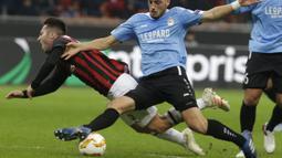 Gelandang AC Milan, Andrea Bertolacci, terjatuh saat berebut bola dengan pemain F91 Dudelange, Edisson Jordan, pada laga Liga Europa di Stadion San Siro, Kamis (29/11). AC Milan menang 5-2 atas F91 Dudelange. (AP/Luca Bruno)