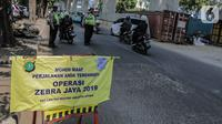 Polisi lalu lintas menggelar Operasi Zebra 2019 di Jalan Boulevard Gading Raya, Jakarta, Kamis (24/10/2019). Operasi selama dua pekan hingga 5 November mendatang tersebut untuk meningkatkan kepatuhan dan kedisiplinan pengendara kendaraan bermotor dalam berlalu lintas. (Liputan6.com/Faizal Fanani)