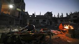 Seorang pria Palestina menjual barang-barang ketika seorang pemuda bersiap untuk memasak jagung dekat bangunan yang hancur selama konflik antara Hamas dan Israel pada Mei 2021 di Beit Hanun, Jalur Gaza, Senin (7/6/2021). Hamas dan Israel gencatan senjata setelah perang 11 hari. (MAHMUD HAMS/AFP)